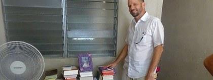 Ds Carlos met zijn bibliotheek, steeds aangevuld door SEZ.