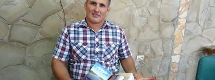 Ds. Ángel laat de boeken zien die hij van sez heeft ontvangen via de post.