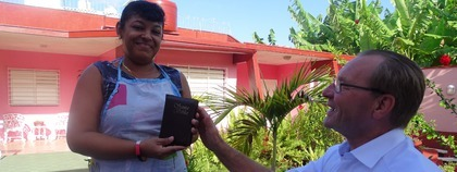 Jan geeft zijn eigen Bijbel aan de werkster in het hotel, Die wel naar de kerk gaat maar graag een eigen Bijbel heeft.